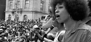 black and white image of angela davis at a rally in the 1960s